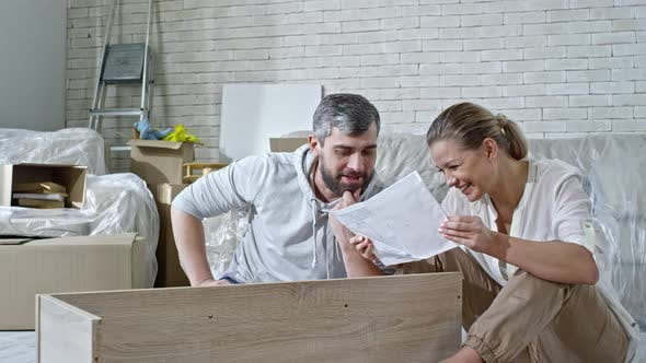 Thumbnail for Laughing Couple Inspecting Assembling Manual for Shelf