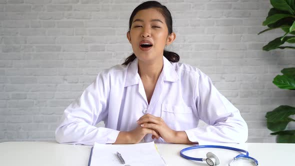 Vue de la vidéo conférence en ligne avec une médecin asiatique et une patiente regardant la caméra