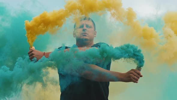 Man with Yellow and Blue Colored Smoke Bomb