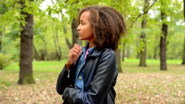 Cover Image for Young African Thoughtful Girl Think About Problems in the Forest - She Looks for Ideas