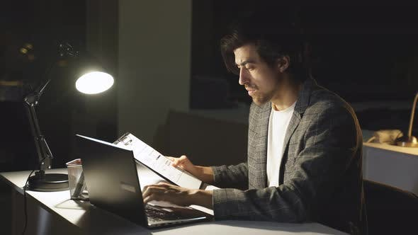 A Focused Office Worker Checks a Business Report a Man Did Not Have Time to Finish Work on Time and