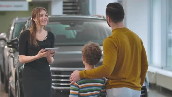 Thumbnail for Back View of Adult Caucasian Man Choosing Automobile with Son in Car Dealership