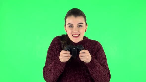 Thumbnail for Girl Playing a Video Game Using a Wireless Controller with Joy and Rejoicing in Victory