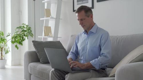 Smiling Middle Aged Man Using Laptop Computer Sitting on Couch at Home