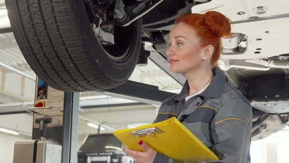 Thumbnail for Female Car Mechanic Examining Wheels of a Car on a Lift, Taking Notes on Clipboard