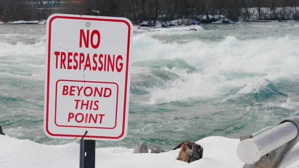 A Plate with an Inscription No Trespassing. Dangerous for Swimming and for Living Place. The Stormy