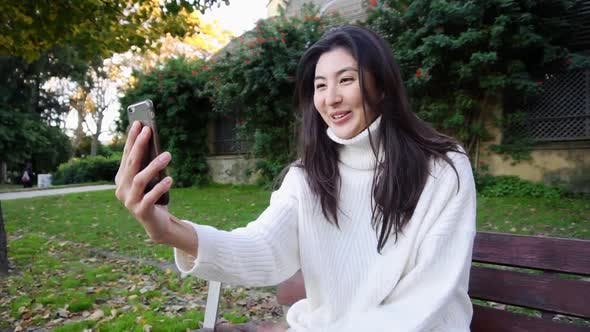 Japanese Girl Sitting on Bench and Making Video Call By Smartphone.