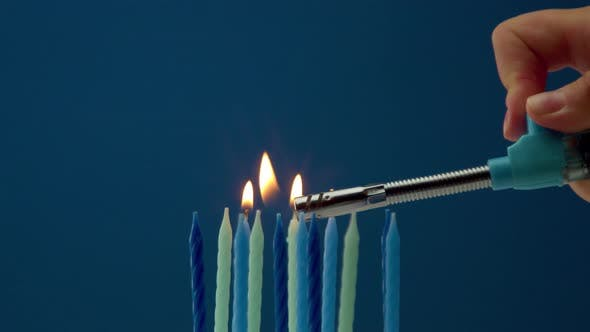Some Cold Tones Candles on Blue Background and Someone Lighting Candles