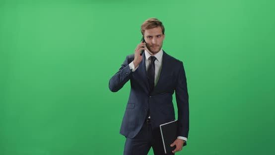 Businessman in a Suit Standing and Talking on a Mobile Phone, Top Manager