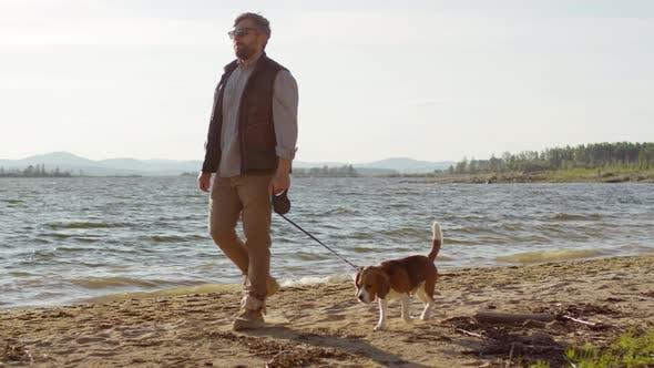 Thumbnail for Mid-Aged Man Enjoying Walk with Dog on Beautiful Lakeshore
