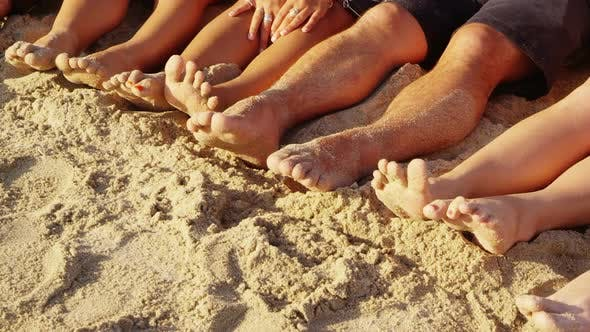 Thumbnail for Group of young people with feet in sand, closeup