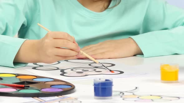 Thumbnail for Little Girl Sits at the Table and Paints Her Drawing. Close Up