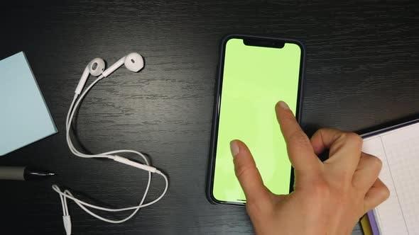 Smartphone mit grünem Bildschirm in der Tabelle. Chroma-Schlüssel