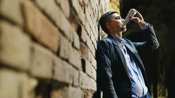 Cover Image for Businessman in a Suit Drinking Alcohol From Flasks. It Should Be in an Abandoned House or Ruins