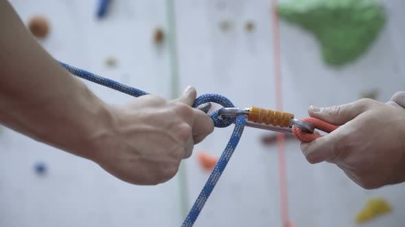 A Rock Climber Tie a Knot on a Rope. A Person Is Preparing for the Ascent. Man Learns To Tie a Knot