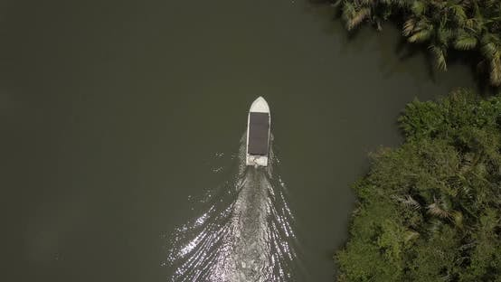Thumbnail for Aerial Top View of Little White Fisherman Boat Sailing Along Beautiful Jungle River with Sun
