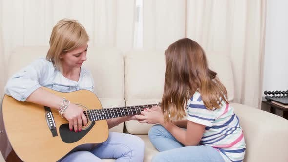 Thumbnail for Daughter Showing To Her Mother How To Play a Song on the Guitar
