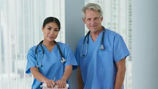 Medium shot portrait of two friendly medical professionals looking at camera