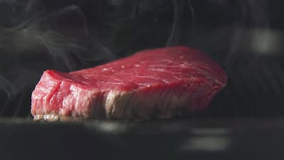 Steak Of Meat Is Cooking On A Grill