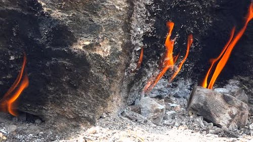 Flame of Methane Underground Emerges From Crack Between Rocks and Burns to Earth