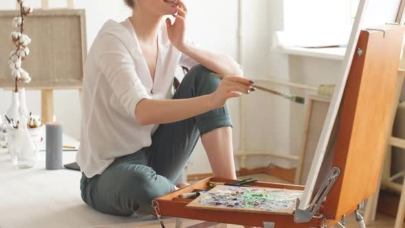 Talented Painter Sitting with Crossed Legs and Enjoying Her Pastime