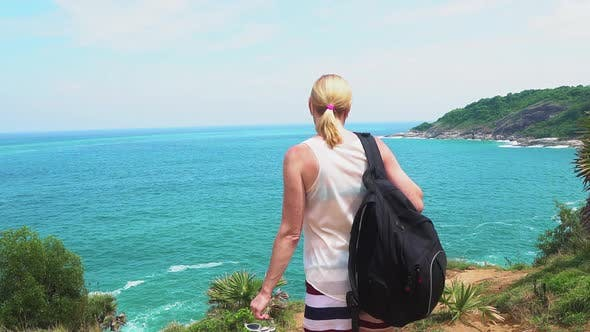Thumbnail for traveler girl looks at a beautiful seascape on the edge of a cliff