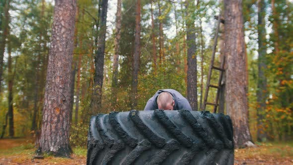 Thumbnail for A Tattooed Man Bodybuilder Pushes Over the Tire on the Ground, Training Outdoors