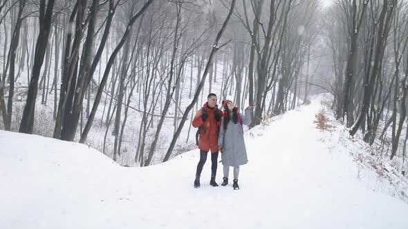 Thumbnail for Couple in the Middle of Forest Enjoying Snowfall