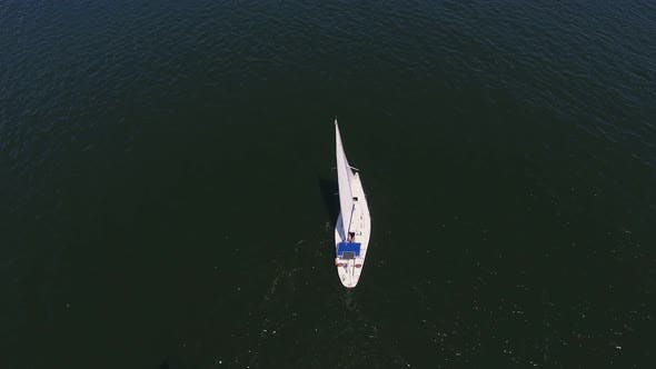 Cover Image for Aerial Shot of a Small Yacht Sailing in the Dnipro on a Sunny Day in Summer