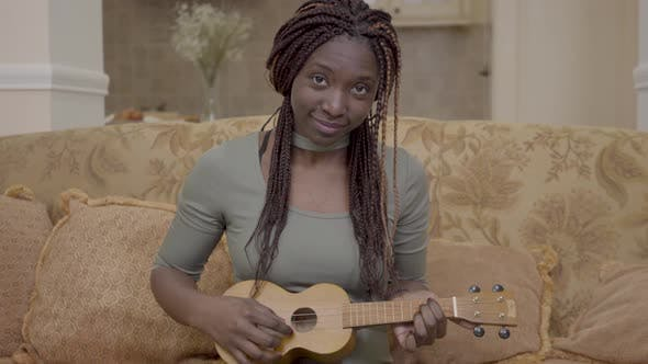 Thumbnail for Portrait of Pretty African American Woman Playing Ukulele Guitar on the Coach in Modern Living Room