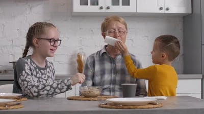 Grandchildren Helping Grandmother During Breakfast