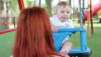Redhaired Woman Shakes Her Young Son on Plastic Swings