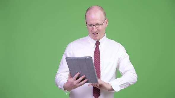 Thumbnail for Happy Mature Bald Businessman Using Digital Tablet and Getting Good News