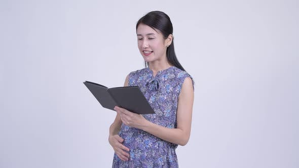 Thumbnail for Happy Pregnant Asian Woman Reading Book