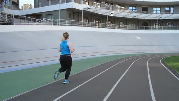Thumbnail for Overweight Female Jogging on City Stadium Track