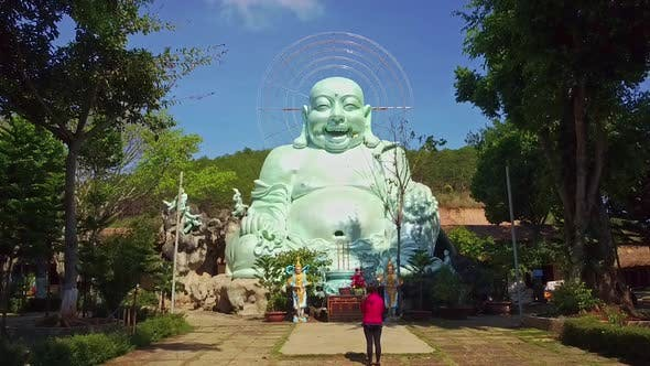 Thumbnail for Flycam Approaches Laughing Buddha Statue in Temple Park
