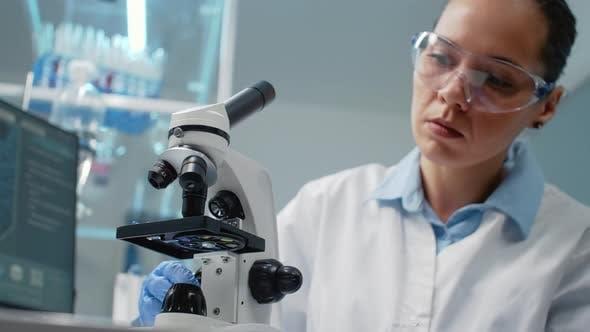 Portrait of Specialist Using Scientific Microscope in Laboratory