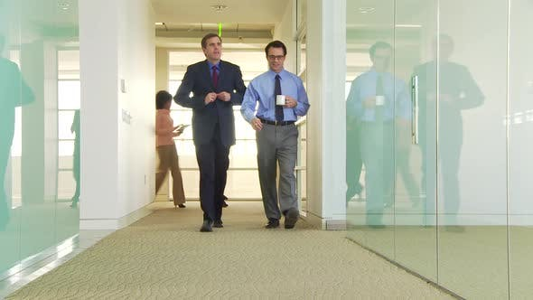 Cover Image for Five business people walking down hallway