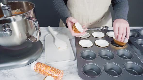 Scooping pumpkin spice cupcake batter with batter scoop into a cupcake pan with liners.