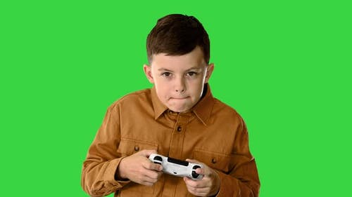 Emotional Little Boy Playing Video Games with Joystick in His Hands on a Green Screen Chroma Key