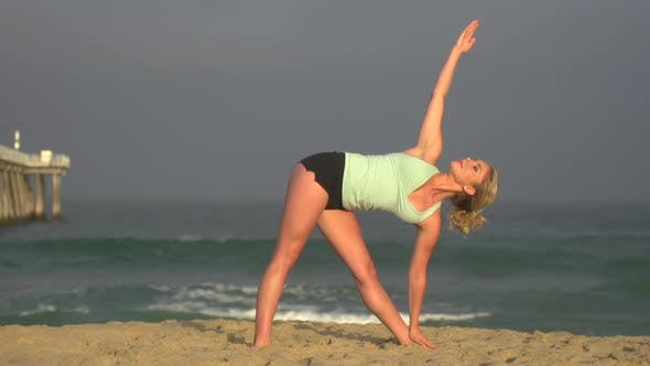 Thumbnail for A young woman does yoga on the beach next to a pier.