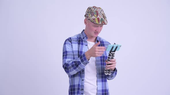 Cover Image for Stressed Young Hipster Man As Vlogger Fixing Phone on Tripod