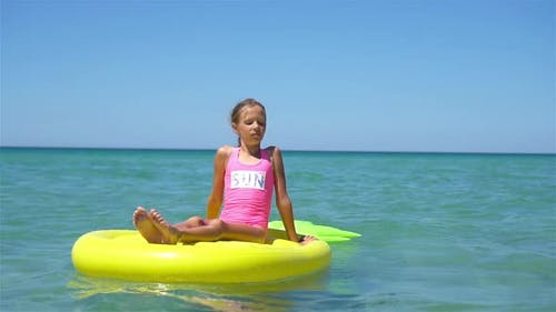 Adorable Girl on Inflatable Air Mattress in the Sea
