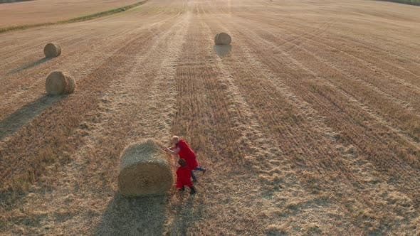 Thumbnail for Drone View of Superheroes Rolling Huge Straw Stack