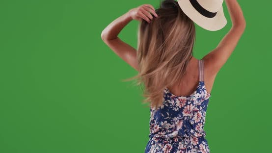 Thumbnail for Rear view of young woman taking off hat and letting down hair on greenscreen
