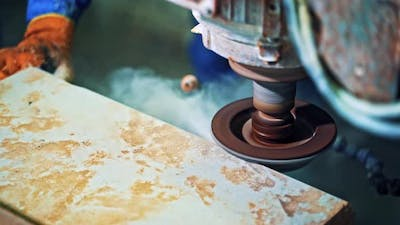 Worker processes granite stone. Grinder worker cuts stone block with electric saw