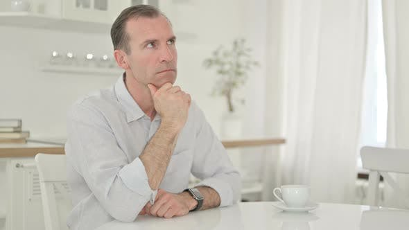 Serious Middle Aged Man Sitting at Home and Thinking