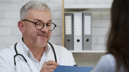 Doctor Talking To Sick Patient Lady Having Appointment In Clinic