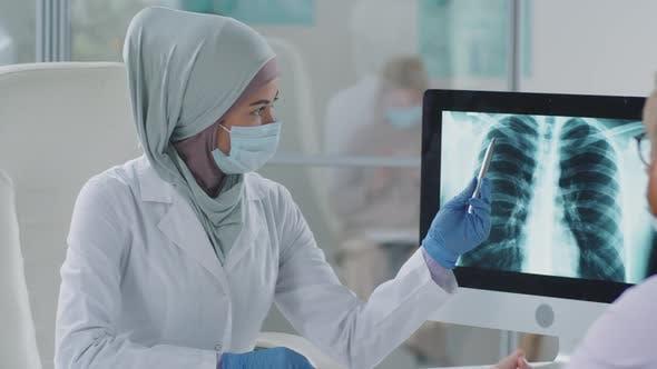 Ärztin in Hijab und Maske erklärt dem Menschen die Röntgenaufnahme der Brust