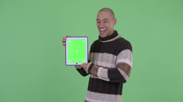 Thumbnail for Happy Bald Multi Ethnic Man Showing Digital Tablet and Looking Surprised